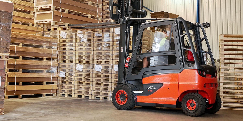 Röd truck i ett lager med pallar och kartonger